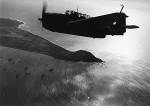 US Navy TBM-3 Avenger over Iwo Jima, Japan, Mar 1945; note Mount Suribachi in center of photo and Allied ships to northwest (left)