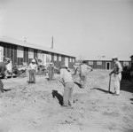 Men digging drainage ditches between barracks buildings, Jerome War Relocation Center, Arkansas, United States, 17 Nov 1942