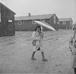 Japanese-American girl walking in rain, Jerome Relocation Center, Denson, Arkansas, United States, 12 Mar 1943