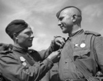 A Soviet soldier being awarded the Defense of Leningrad medal, 1 Jun 1944