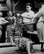 A French mob shaved the head of a French girl as punishment for having personal relations with a German soldier, Mont?limar, France, 29 Aug 1944