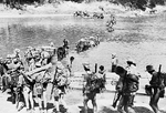 A column of Chindit irregular troops crossing a river in Burma, Feb-Mar 1943