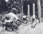 A Japanese soldier tending graves of fallen comrades, Malaya, circa Dec 1941-Feb 1942