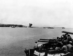 40mm gun crew of an unidentified American cruiser watched as lighter vessels shelled a Japanese storage dump (note smoke in center), Asan Beachhead, Guam, Mariana Islands, 21 Jul 1944