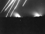 Star shells in the sky and fires burning on the ground illuminated the city of Garapan at night, Saipan, Mariana Islands, Jul 1944