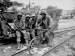 African-American men of the US Marine Corps Third Ammunitions Company at Saipan, Mariana Islands, Jun 1944; Pfc Boykin on bicycle; Pfcs Anthony, Shackelford, and Purdy watching
