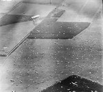 Reconnaissance photograph showing Dakota aircraft dropping paratroopers of 1st Airborne Brigade on to Dropping Zone