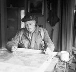 Brigadier P. H. W. Hicks studying a map at Divisional Headquarters during the advance to Arnhem, Netherlands during Operation Market Garden, 18 Sep 1944