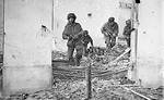 Four British paratroopers with Sten sub-machineguns moving through a shell-damaged house in Oosterbeek, the Netherlands to which they had retreated after being driven out of Arnhem, 23 Sep 194