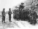 Two New Zealand soldiers guarding a group of German prisoners of war, Monte Cassino, Italy, Mar 1944
