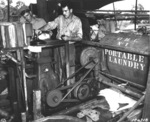 US Army Privates Mearl Hatfield and Clen C. Campbell operating the portable laundry diesel engine, New Guinea, 19 Apr 1943