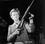 Female factory worker posed with finished Sten sub-machinegun, Small Arms Plant, Long Branch, Ontario, Canada, 26 May 1942