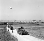 Vehicles of 4th County of London Yeomanry, UK 7th Armored Division moving inland from Gold Beach, Normandy, France, 7 Jun 1944; note Cromwell tank leading the column