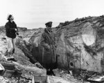 US Navy Lieutenant Commander Knapper and Chief Yeoman Cook of USS Texas examining a damaged German pillbox at Pointe du Hoc, Normandy, France, 6 Jun 1944; note covered dead US Army Ranger at right