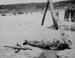 Next to a fallen soldier, a fellow comrade formed a cross with rifles to pay his respects, Normandy, France, Jun 1944