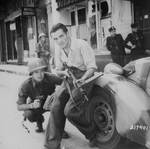 An American officer and a French partisan with a Sten sub-machinegun crouched behind a car during a street fight in a French city, Jun 1944