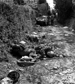 Three dead German soldiers laying on a road near Sainteny, Normandy, France, 16 Jul 1944; note Volkswagen-made Schwimmwagen vehicle and two American soldiers in background