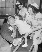 American Private First Class Lee Harper, wounded at Normandy, was greeted by his 2-year-old sister Janet, whom he had never seen before, as his mother and wife looked on, New York City, 1 Aug 1945