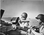 Two Ohio United States Coast Guard men, John R. Smith and Daniel J. Kaczorowski, at their gun aboard a transport off Normandy, circa Jun 1944