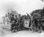 American troops posing with a captured Nazi flag and a wrecked German tank, Chambois, France, 20 Aug 1944