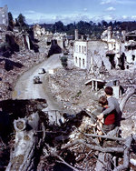 Two French boys watched from a hilltop as Allied vehicles passed through the badly damaged city of Saint-Lô, France, circa Jul-Aug 1944