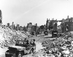 View of the town of Valognes, devastated by Allied bombing during the Cherbourg battle, 24 Jun 1944; note jeep
