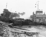 Broached landing craft during the Normandy storm, probably at Omaha Beach, 21 Jun 1944; note LST-543 in background
