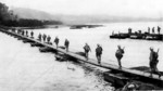 US Army soldiers crossing the Machinato Inlet on foot bridge, Okinawa, Japan, morning of 19 Apr 1945