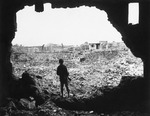 A US Marine observing ruined buildings in Naha, Okinawa, Japan, 13 Jun 1945