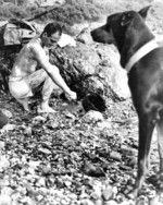 US Marine Private First Class Fred Muscard cleaning himself while his war dog Lux stood on guard, Okinawa, Japan, Apr 1945
