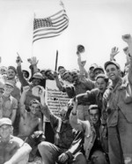 US Marines and US Army soldiers celebrating the capture of Hill 89, Okinawa, Japan, 27 Jun 1945; the hill was captured by US Army 7th Inf Div on 21 Jun