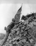 US Marine Lieutenant Colonel R. P. Ross, Jr. raising an US flag over Shuri castle on Okinawa, Japan, 29 May 1945, photo 1 of 2