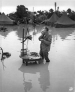 US Marine Staff Sergeant A S. Barnacle shaving in his camp on Okinawa, Japan, ignoring the heavy flooding due to rain, 28 May 1945