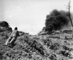 US Marine observing a Japanese position as a flame thrower attacked it, Okinawa, Japan, May 1945