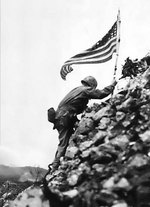 US Marine Lieutenant Colonel R. P. Ross, Jr. raising an US flag over Shuri castle on Okinawa, Japan, 29 May 1945, photo 2 of 2