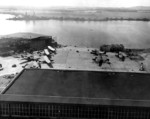 View of Naval Air Station Ford Island, Oahu, US Territory of Hawaii, 8 Dec 1941 from the Ford Island water tower; note PBY aircraft on the ramp and USS Nevada after her move from Hospital Point to the Waipio Peninsula