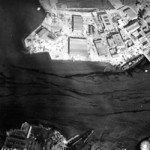 Aerial view of Naval Air Station Ford Island, Oahu, US Territory of Hawaii, 10 Dec 1941; note damaged PBY aircraft, USS Curtiss, and USS Shaw