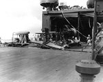 Damage to hangar doors of seaplane tender USS Curtiss by Japanese 250kg bomb during Pearl Harbor attack, 7 Dec 1941, photo 2 of 2; note wreckage of OS2U-2 floatplane in foreground