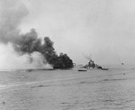 APD Ward burning in Ormoc Bay, Leyte, Philippine Islands, after being struck by special attack aircraft, 7 Dec 1944; the firefighting ship was destroyer O