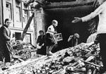Polish civilians salvaging items from a pile of rubble that used to be their homes, Warsaw, Poland, Sep 1939; note boy with caged canary