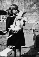 A girl holding her dog in a devastated neighborhood in Warsaw, Poland, 5 Sep 1939