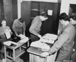 US Army Lieutenant A. H. Hadden and his staff working on passes issued to participants of the Potsdam Conference, Germany, 14 Jul 1945