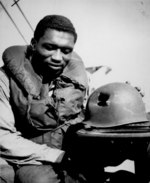 African-American US Coast Guardsman Fireman 1st Class Charles Tyner displaying his helmet, damaged by large shrapnel during the invasion of Southern France, circa late 1944