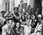 US Army Private George Katere, Private First Class William Mosa, and Private First Class Jessie Hampton posing with Sicilian civilians, Italy, 11 Jul 1943