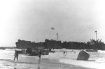 LCVPs from APAs Barnett and Monrovia unloaded supplies onto the beach near Gela, Sicly, 10 Jul 1943; note LST-344 and LST-338 in background
