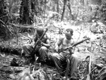 Sergeant John Cark and Staff Sergeant Ford Shaw of E Company, 25th Combat Team, US Army 93rd Division cleaning their rifles alongside the East West Trail, Bougainville, Solomon Islands, 4 Apr 1944