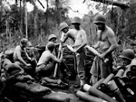 Mortar men of US 1st Marine Division firing against a Japanese artillery position, Cape Gloucester, New Britain, Bismarck Archipelago, circa 15-25 Dec 1943