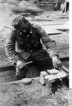 A German Army sergeant roasting bread on a small fire, Stalingrad, Russia, Nov 1942