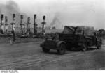 A German truck driving through the ruins of Stalingrad, Russia, with columns of smoke visible in background, Sep 1942