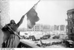 Soviet soldier waving a red flag at a building off the central square in Stalingrad, Russia, Jan-Feb 1943